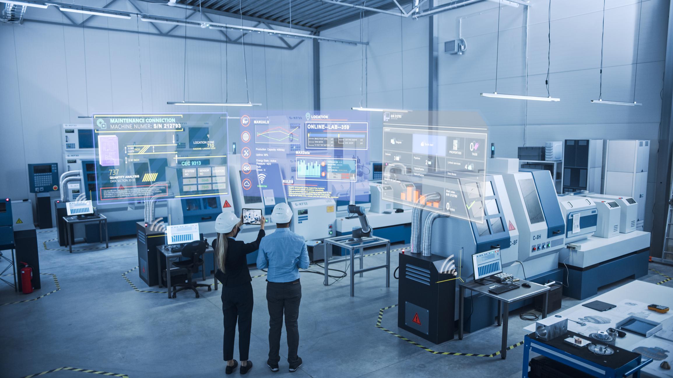 2 ingegneri con tablet usano AI per connettersi a macchinari high tech e visualizzano schermate di manutenzione predittiva e diagnostica