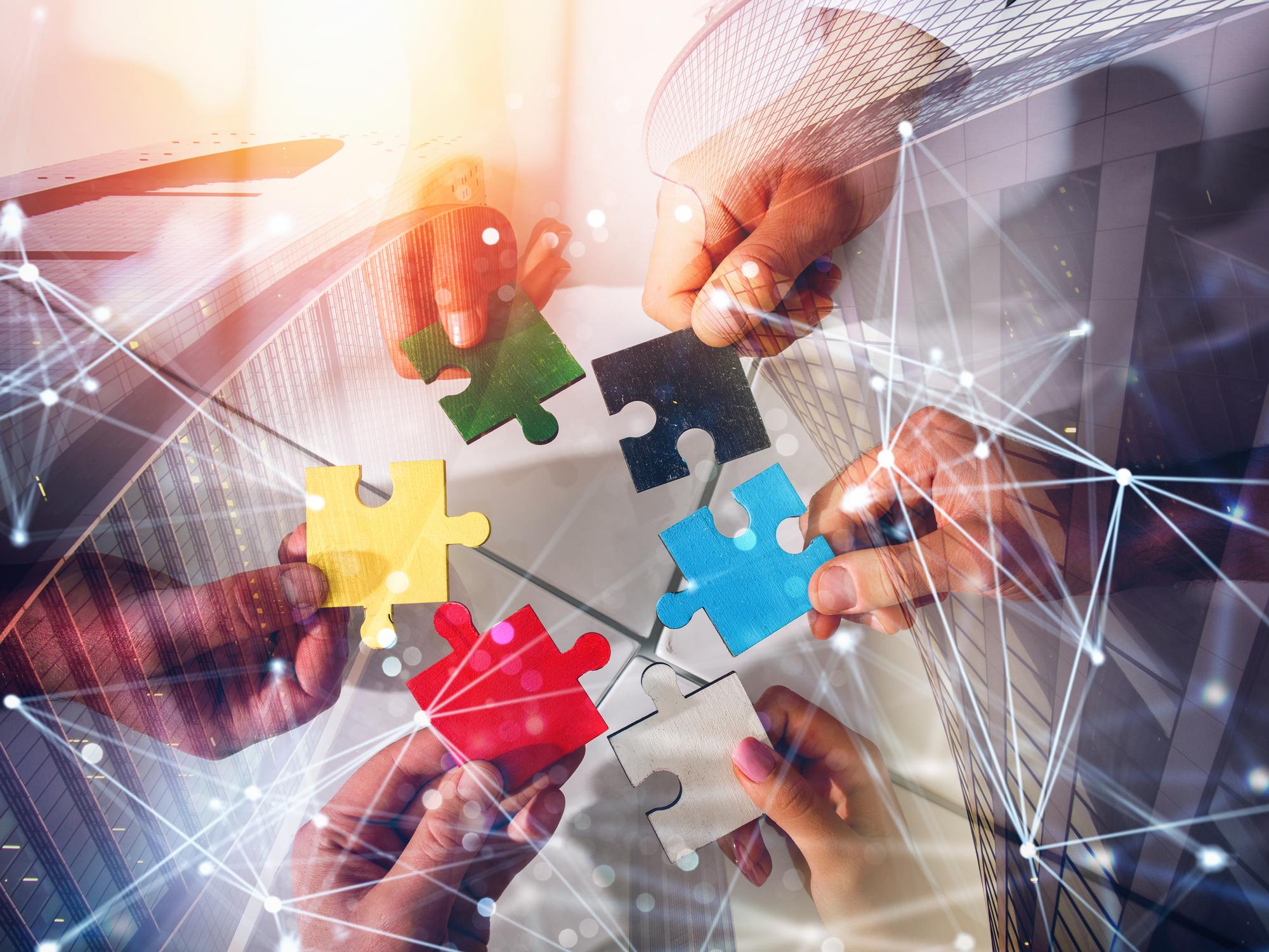 Mani uniscono pezzi puzzle con sfondo uffici e connessione